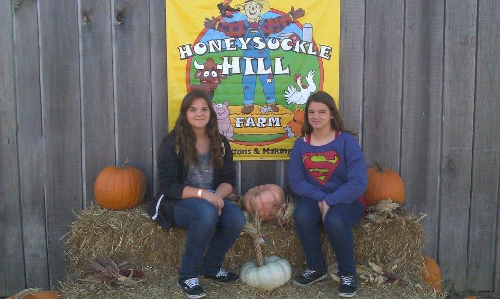 girls at Honeysuckle Hill Farm sign