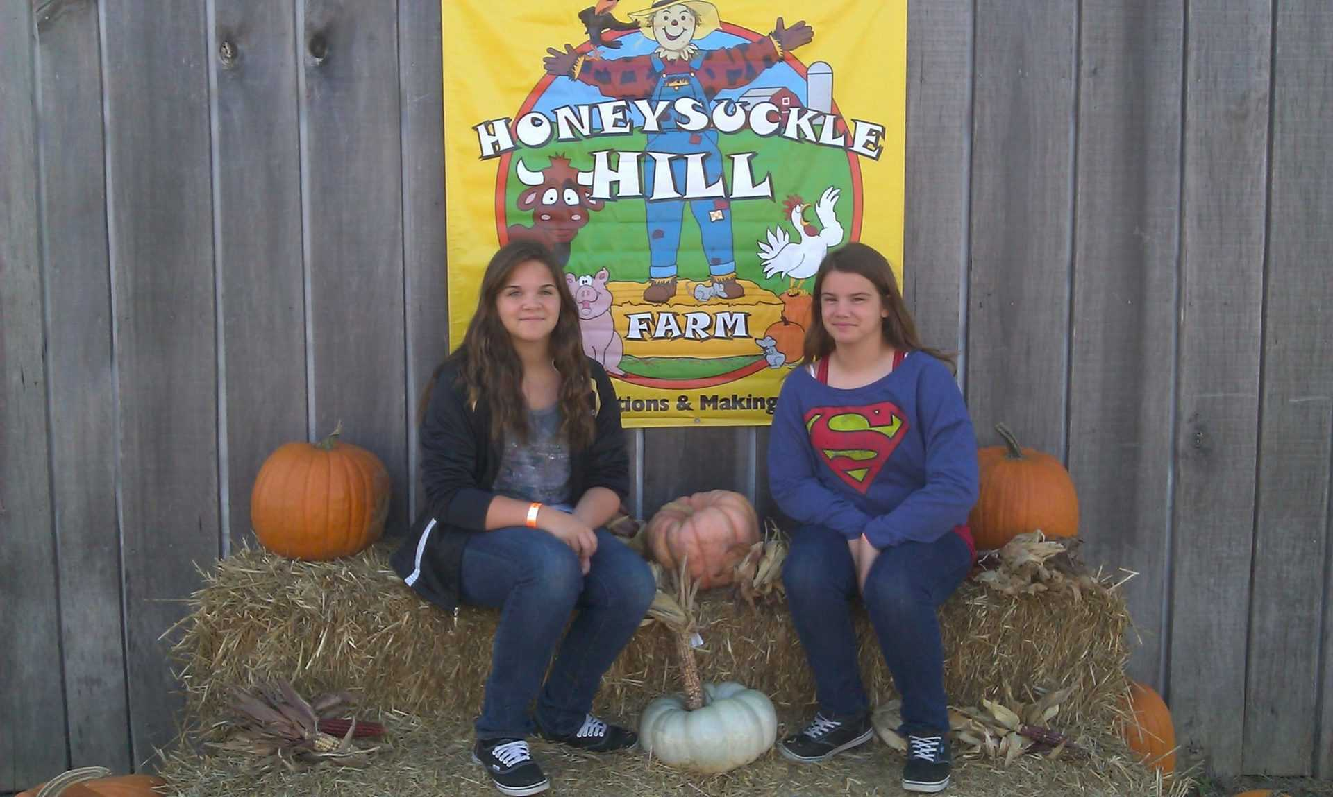 girls at Honeysuckle Hill Farm sign