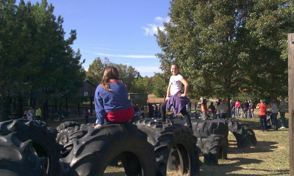 girls play on tires at Honeysuckle Hill Farm