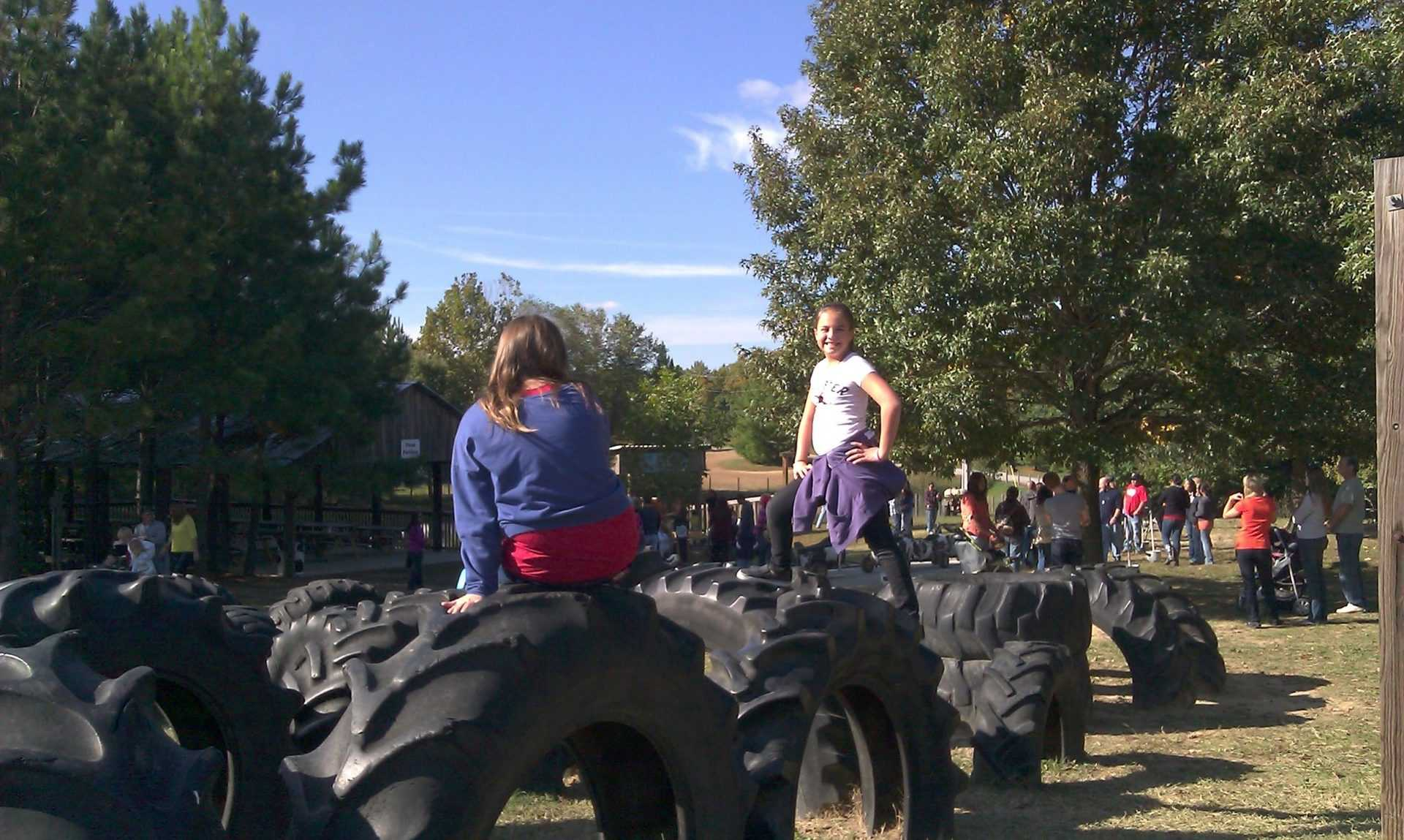 girls play on tires at Honeysuckle Hill Farm