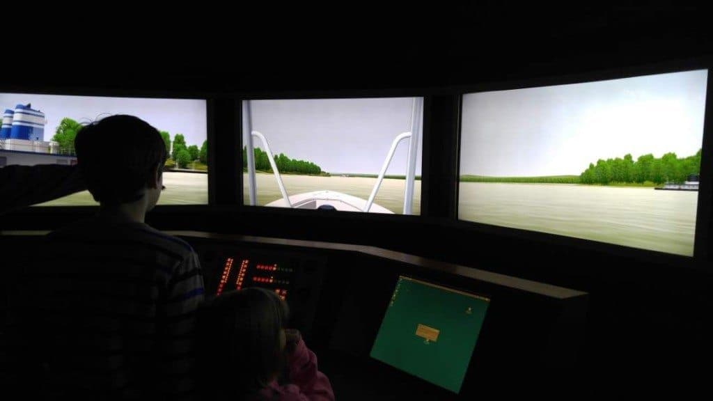 Two kids driving a pilot boat in the simulator at the River Discovery Center in Paducah, Kentucky.