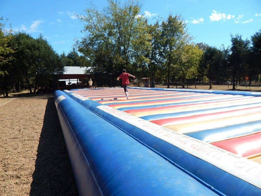 A boy running on the gigantic inflatable jump pad at Lucky Ladd Farms