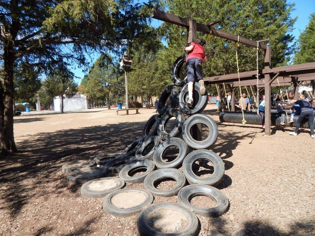A boy climbing tires that create a ladder at Lucky Ladd Farms