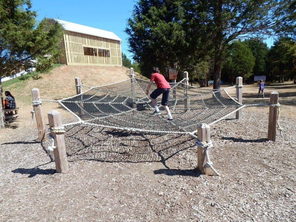 A boy crossing a spider web made of rope at a playground at Lucky Ladd Farms
