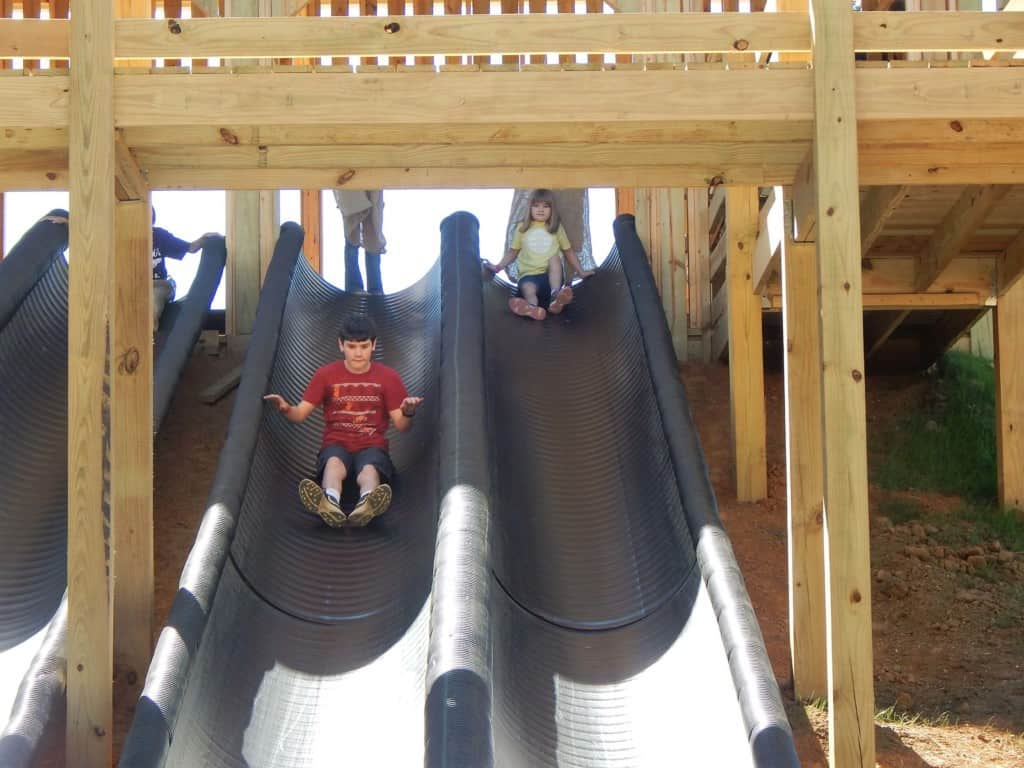 A boy sliding down a long black slide at Lucky Ladd Farms