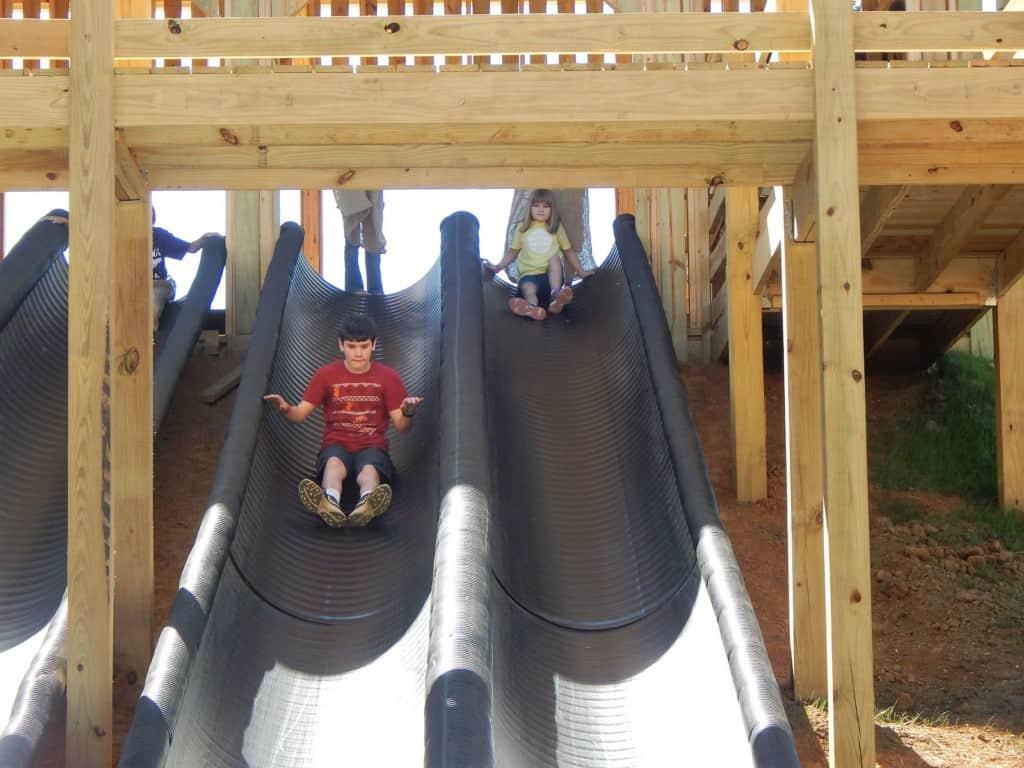 A boy sliding down a long black slide at Lucky Ladd Farms