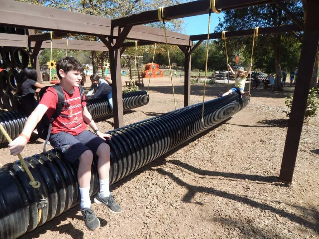 A boy sitting on top of a large tube swing at Lucky Ladd Farms