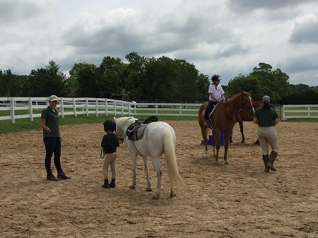 Kids riding horses in a ring at Peachtree Farms Equestrian Camp