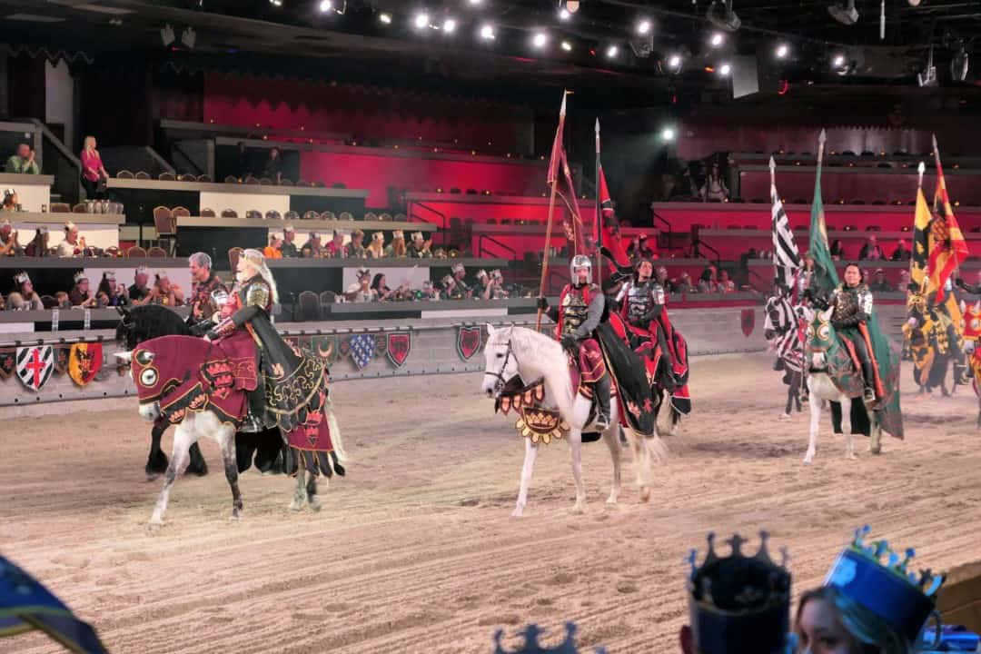 The king parades in the ring followed by his knights at medieval times