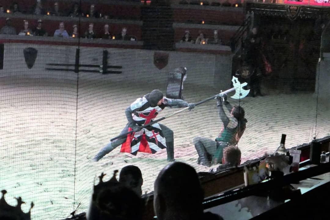 Two knights fighting, one with a sword and the other with an ax at Medieval Times