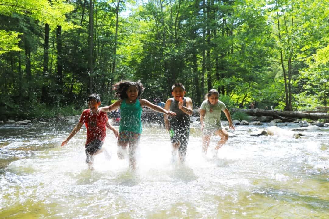 Tremont kids running through a creek