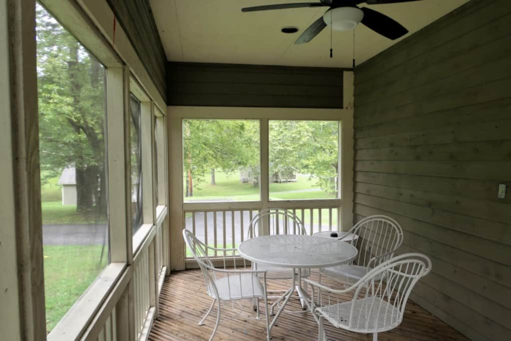 Screened in porch with a table, four chairs, and ceiling fan