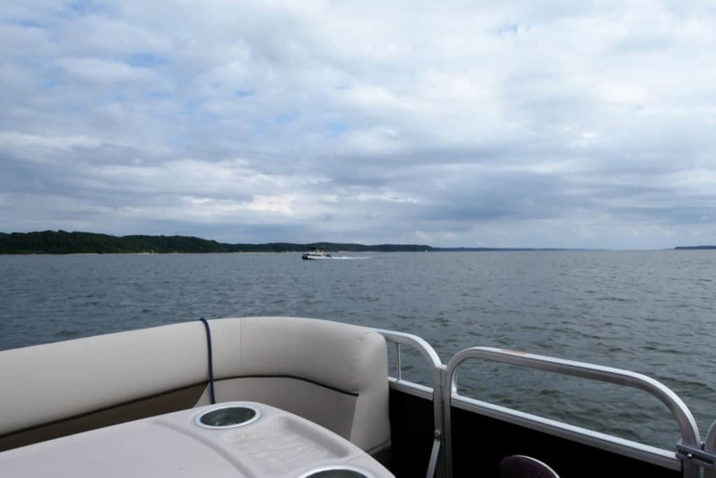 View from a pontoon boat in the middle of Kentucky lake including a passing boat and a cloudy sky.