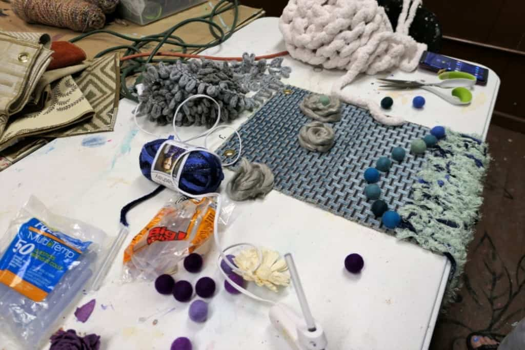 Blue fabric, yarn, and other textiles used to create a wall hanging at Make Paducah.