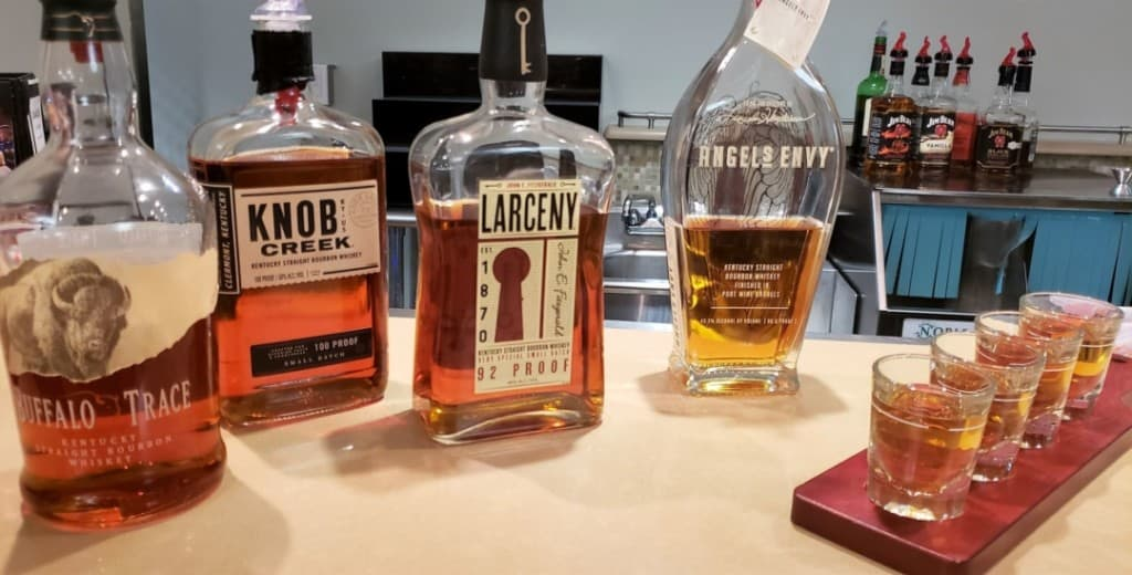 Four different bottles of bourbon and four sample shots; one of each drink.